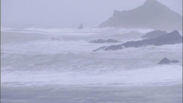 storm waves break against boulders and cliffs along an a coast. - felsblock stock-videos und b-roll-filmmaterial