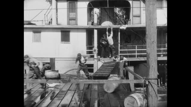 vidéos et rushes de 1928 storm winds destroy a dock, releasing a steamboat - 1928