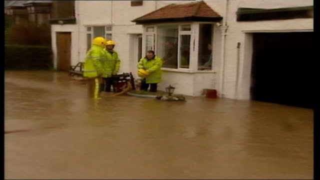 pembrokeshire group of fire fighters standing in flood water beside pump in front of house pull out bv fire fighter standing at front door ms hose... - pembrokeshire stock videos & royalty-free footage