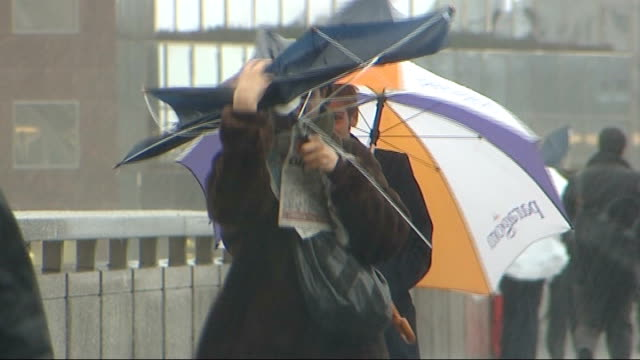 Commuters using umbrellas on London Bridge Good shots of commuters along on London Bridge in torrential rain including woman with broken umbrella and...