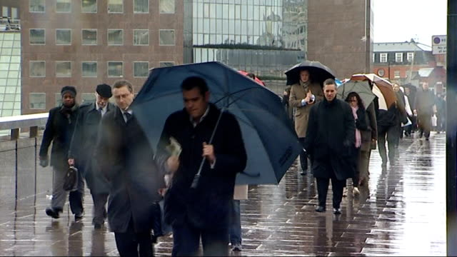 Commuters using umbrellas on London Bridge ENGLAND London London Bridge Good shots of commuters along on London Bridge many carrying umbrellas to...