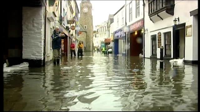 Storms batter Britain disrupting travel and power Devon Flooded street Emergency services members wading through flood water Man in doorway behind...