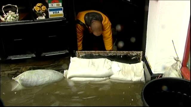 Storms batter Britain disrupting travel and power Devon Man in doorway behind semisubmerged sandbags in flooded street