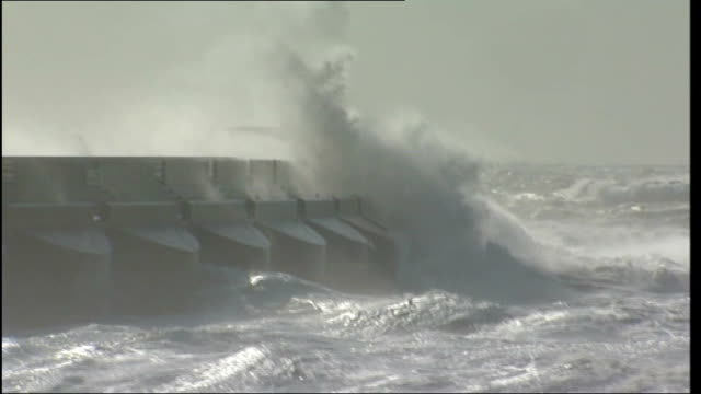 storms batter britain disrupting travel and power; england: kent: dover: huge waves breaking against flood barricade - barricade stock videos & royalty-free footage