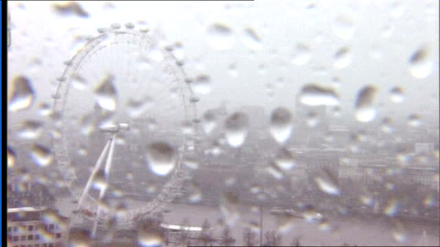 Storms batter Britain disrupting travel and power London Eye Vox pop Waterlogged park People along in rain Rain falling on wet pavement