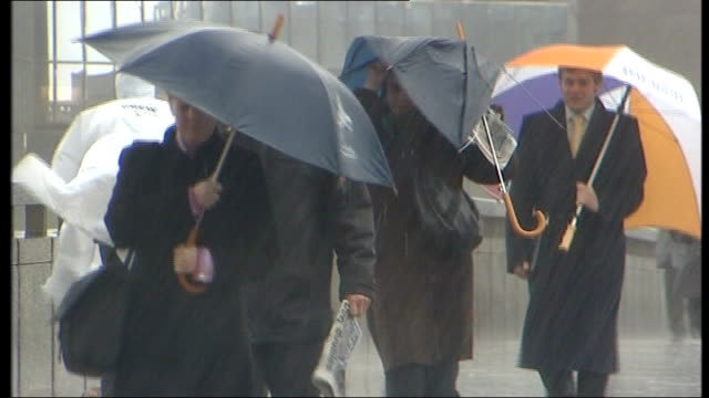 Storms batter Britain disrupting travel and power London Commuters along with umbrellas in torrential rain