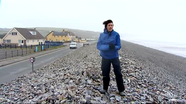Storms batter Britain disrupting travel and power WALES Pembrokeshire Newgale Reporter to camera Waves crashing onto stony beach Newsurf Beach Shop...
