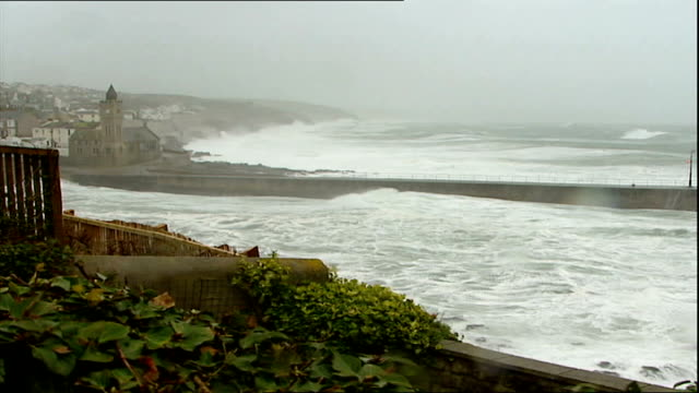 Storms batter Britain disrupting travel and power Waves breaking against bay of coastal town