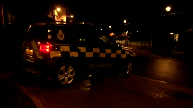 more storms hit flooded south west Britain ENGLAND Bude NIGHT 'Coast guard' vehicle 'Road Closed' sign and bollards on road Low angle view sandbags...