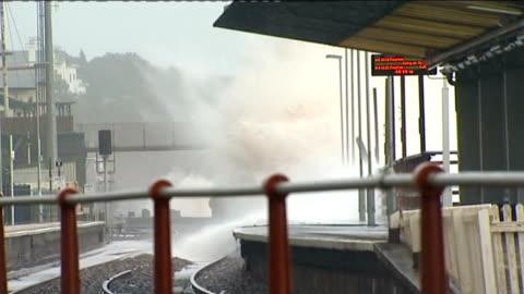 storms in south west england: dawlish railway line; england: devon: dawlish: ext sea water crashing beneath railway bridge / huge waves crashing onto... - devon stock videos & royalty-free footage