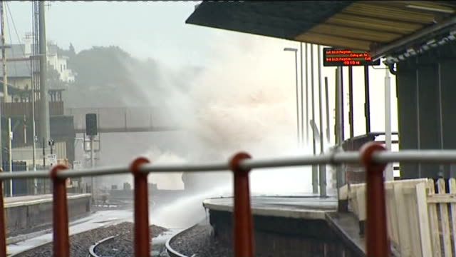 storms in south west england: dawlish railway line; england: devon: dawlish: ext sea water crashing beneath railway bridge / huge waves crashing onto... - devon stock videos & royalty-free footage