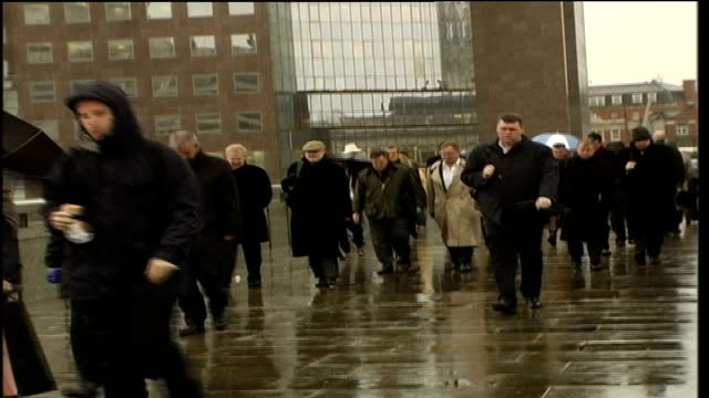 Storms kill 11 people and cause countrywide destruction ENGLAND London People walking along on bridge in high winds People carrying umbrellaswalking...