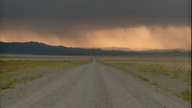 stockvideo's en b-roll-footage met ws, stormy clouds above empty dirt road in desert with mountains in distance, tonopah, nevada, usa - oneindigheid