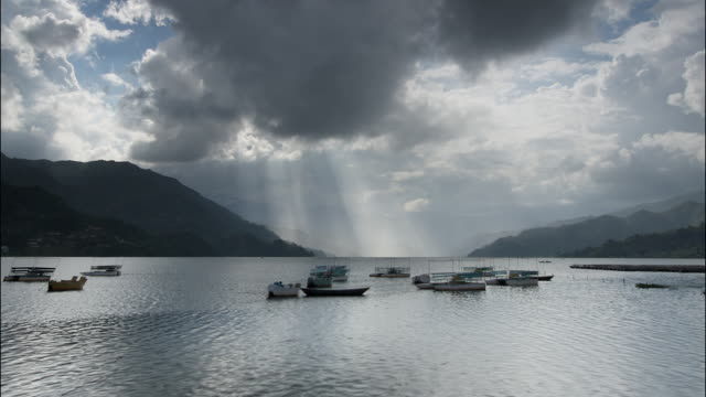 T/L stormy clouds over boats on the Pokhara lake, Himalayas