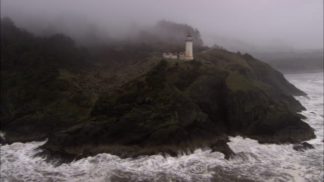 a stormy ocean surges at a foggy, rocky coastline with a lighthouse. - leuchtturm stock-videos und b-roll-filmmaterial