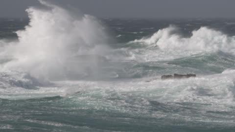 vídeos de stock, filmes e b-roll de stormy sea crashes onto rocky shore, cornwall, uk - oceano atlântico
