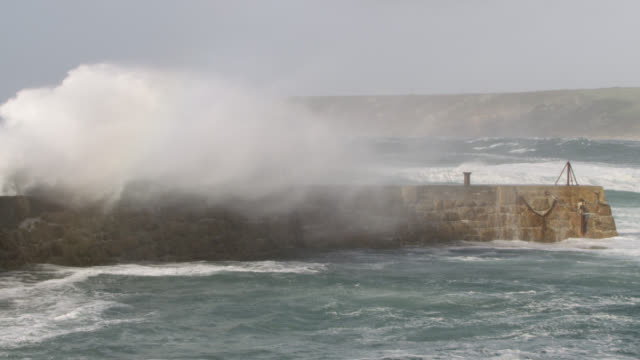 stormy sea crashes over harbour wall, cornwall, uk - power in nature stock videos & royalty-free footage