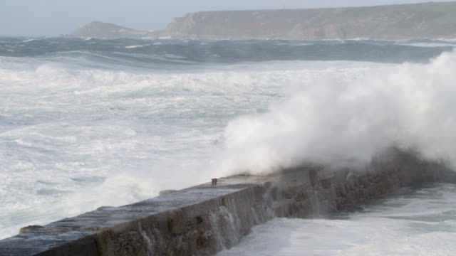 stormy sea crashes over harbour wall, cornwall, uk - cornwall england stock videos & royalty-free footage
