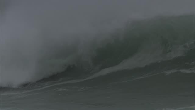 Stormy sea rolls in onto rocky shore, New Zealand