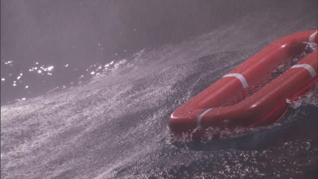 vídeos de stock e filmes b-roll de a stormy sea tosses around an empty orange life raft. - barco salva vidas