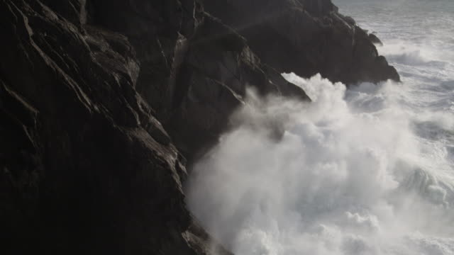 stormy seas hitting rocky coast - fels stock-videos und b-roll-filmmaterial