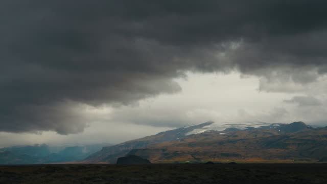 A stormy sky over the plains before the the Eyjafjallajokull or Eyjafjalla Glacier in Southern Iceland in the background