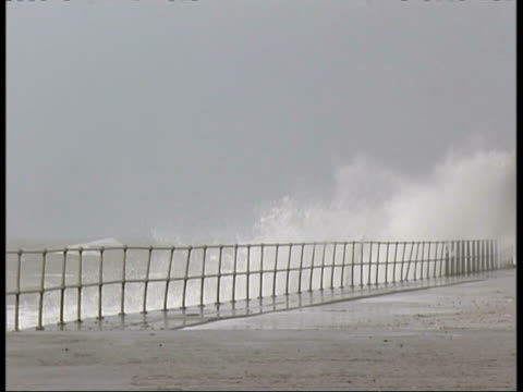 mwa stormy waves crashing in to sea wall, spray splashing over wall - roll over stock videos and b-roll footage
