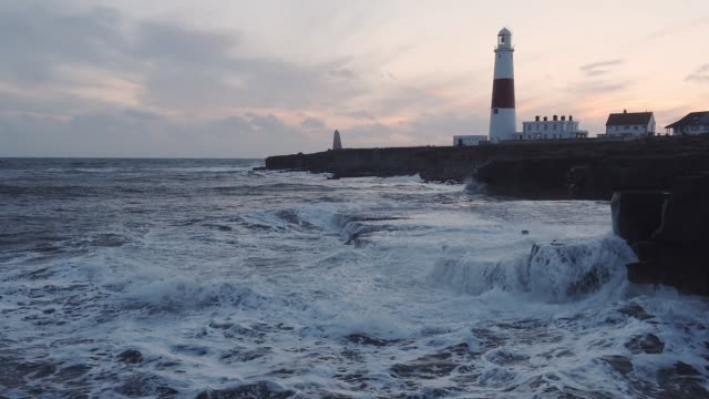 stormy waves crashing on the coastline near portland bill lighthouse, at dusk - coastline stock videos & royalty-free footage