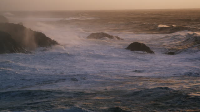 stormy waves lash a rocky shore at dusk - coastal feature stock videos & royalty-free footage