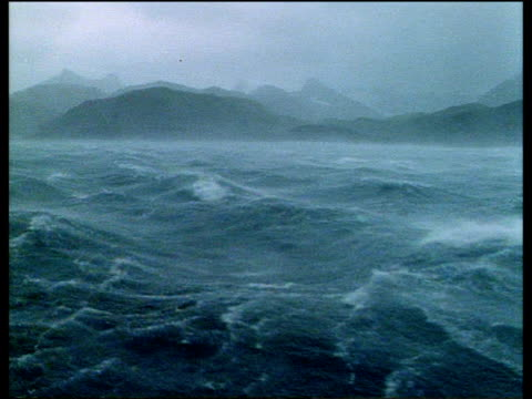 stormy winter sea with sheets of rain, misty land in background, antarctica - nebbia video stock e b–roll