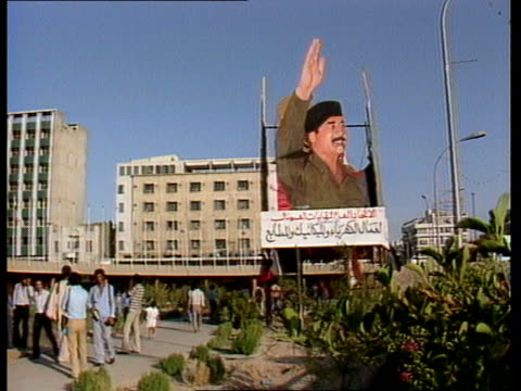 story 2 a nat iraq baghdad ext lms street with huge poster of saddam hussein president of iraq / ms fountains pan traffic towards / ms soldiers and... - iraq stock videos & royalty-free footage