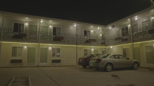 n-d 2 - story motel, 2 cars parked; man walks by on 2nd floor; zoom in to bottom floor room - night - generic location stock videos & royalty-free footage