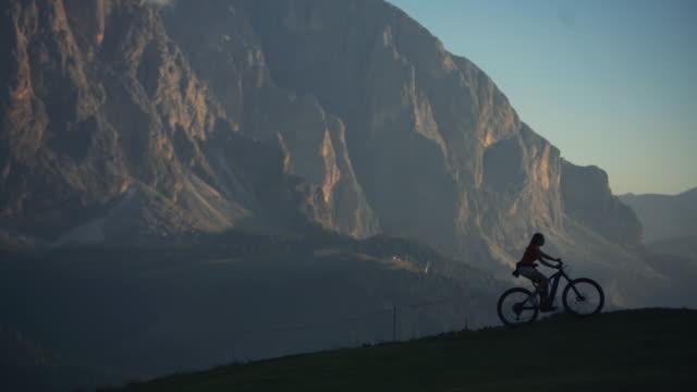 vídeos y material grabado en eventos de stock de narración de un día de senderismo y escalada en los dolomitas: hombre y mujer juntos - mountain bike