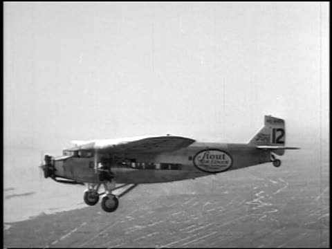 b/w 1927 aerial air-to-air stout air lines airliner flying over land + river / newsreel - air vehicle stock videos & royalty-free footage