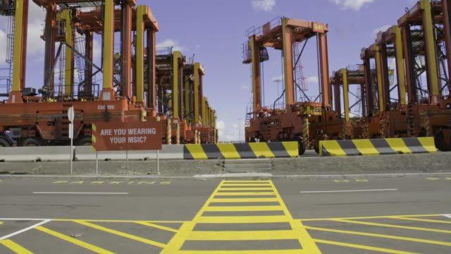 straddle carrier container cranes set off at start of shift, port melbourne - straddle carrier stock videos & royalty-free footage