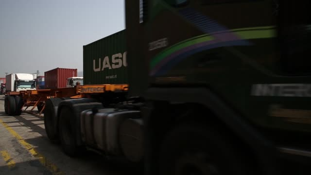 a straddle carrier moves a container onto a truck parked at the uiwang inland container depot in uiwang south korea on monday march 30 trucks drive... - straddle carrier stock videos & royalty-free footage