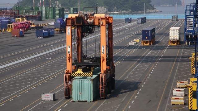 a straddle carrier picks up a shipping container at the bnct co container terminal at busan new port in busan south korea on thursday july 30 2015 - straddle carrier stock videos & royalty-free footage