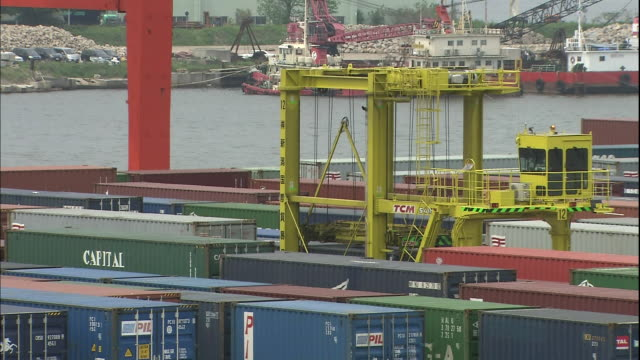 a straddle carrier removes an international container from the container yard at niigata east port. - straddle carrier stock videos & royalty-free footage