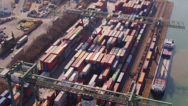 straddle carrier transferring shipping containers in port of dortmund - aerial view - straddle carrier stock videos & royalty-free footage