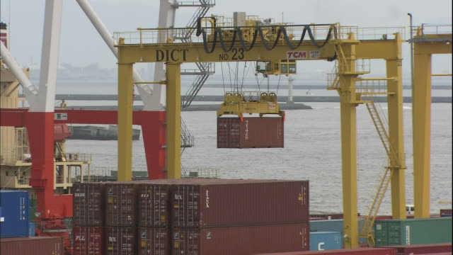 a straddle carrier transports a container over the osaka south port in japan. - straddle carrier stock videos & royalty-free footage