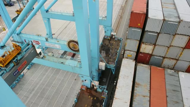 vídeos de stock, filmes e b-roll de straddle carriers operate on the dockside at the port of rotterdam during loading operations for the maersk mckinney moeller triplee class ship... - de perna aberta