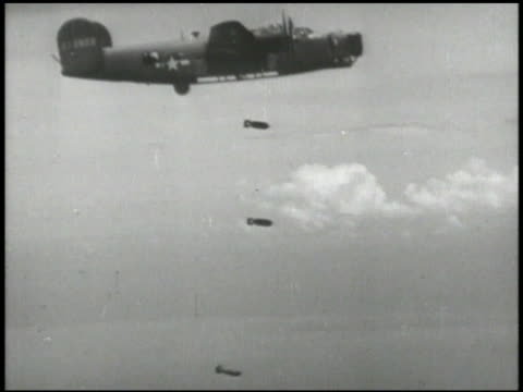 strafing run along beach aerial beside consolidated b24 'liberator' four engine heavy bomber dropping bombs ms many bombs passing close falling... - united states airforce stock videos & royalty-free footage