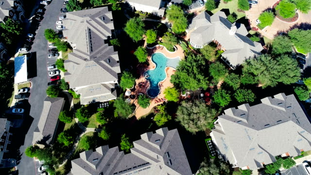 straight down above curvy modern pool surrounded by apartment buildings in modern suburb austin living - tract housing stock videos & royalty-free footage