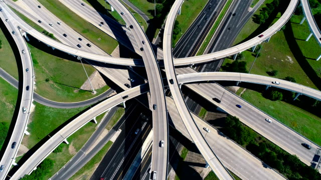 straight down drone angle moving across huge infrastructure transportation overpass highway turnaround in austin , texas , usa - autostrada interstatale americana video stock e b–roll