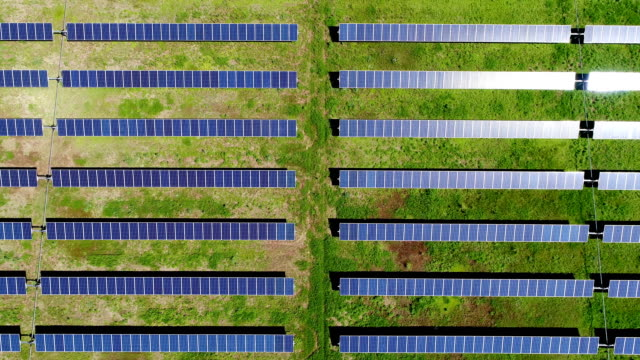 vídeos de stock e filmes b-roll de straight down straight rows solar panel power plant providing clean renewable energy to help fight against climate change and create jobs - painel solar