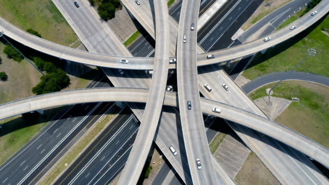 straight down symmetrical angle above interchange transportation traveling on the modern futuristic highway system - autostrada interstatale americana video stock e b–roll