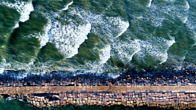 Straight Down View Above Jetty with waves washing on shore at an angle