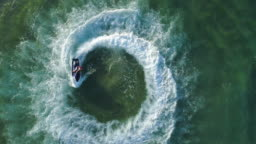 4K straight down zoom out spectacular aerial  view of man having fun riding a personal watercraft in the ocean making a circular pattern, Mozambique