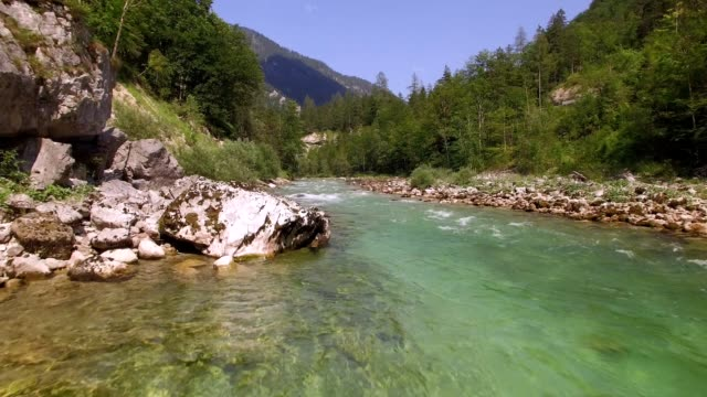 Straight drone flight tight over a mountain river with clear water on a sunny summer day