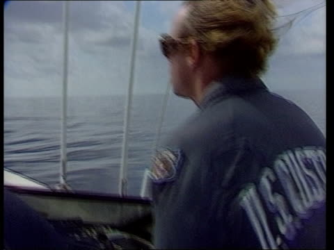 usa straits of florida ext spray from stern of customs agents' patrol boat / patrol boat crew / bow through water / customs official buttoning shirt... - 麻薬点の映像素材/bロール